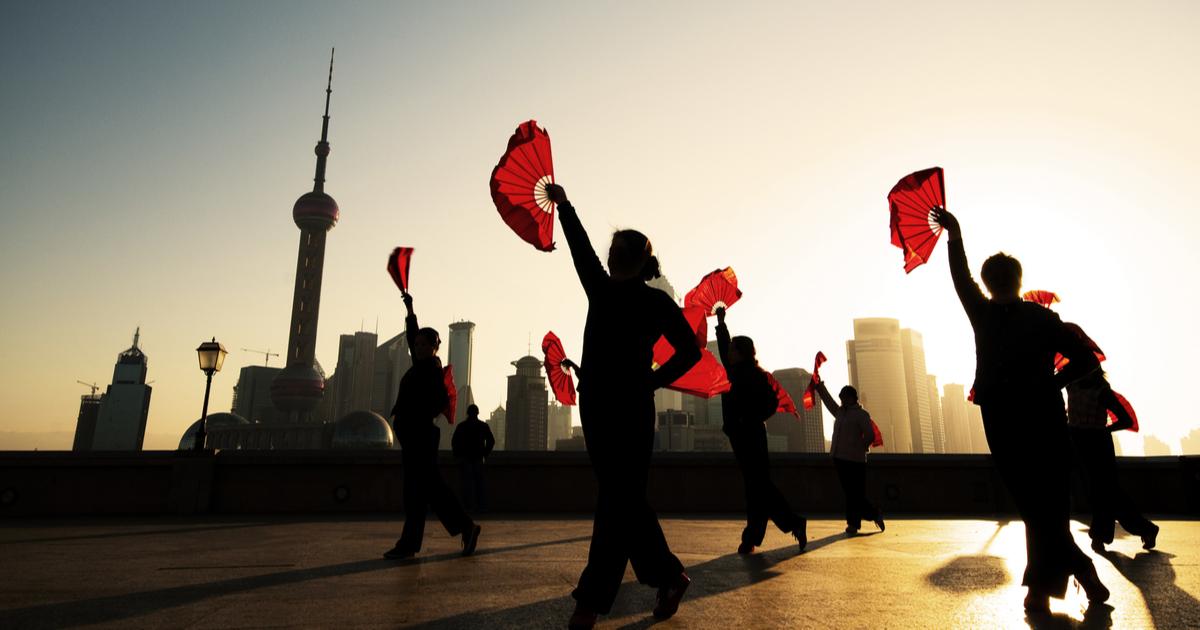 中国の街並みを背景に踊る人の写真